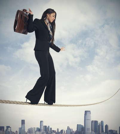 Concepto de riesgo en los negocios con la empresaria en la cuerda Foto de archivo