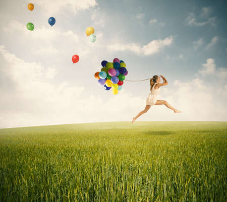 Jumping with balloons in a green field photo