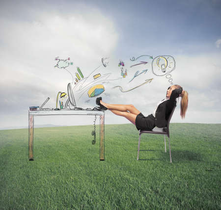 download: Successful businesswoman relaxing on a green field Stock Photo