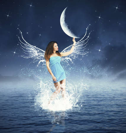 Creative fashion with fairy touching the moon photo