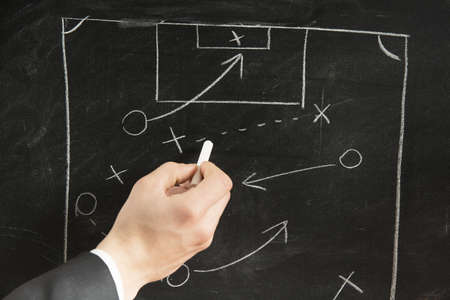 Drawing a Soccer strategy schema in a blackboard photo
