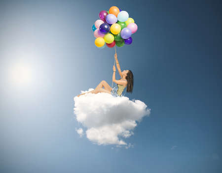 Girl flies over a soft cloud Stok Fotoğraf
