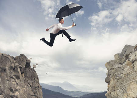 impediment: Businessman jumping over the mountains
