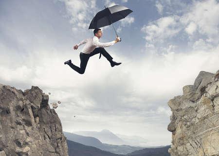 Zakenman springen over de bergen Stockfoto