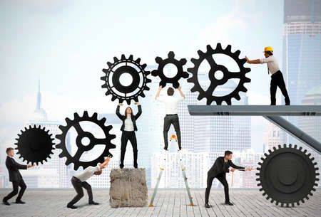 energy work: Teamwork works together to build a gear system Stock Photo