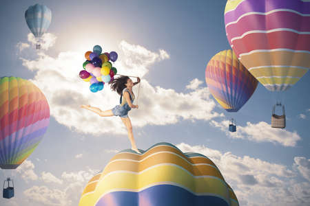 to inflate: Happy girl jumping over hot air balloon Stock Photo