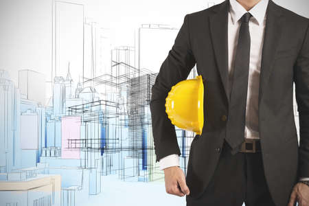 construction project: Ready businessman architect with yellow helmet