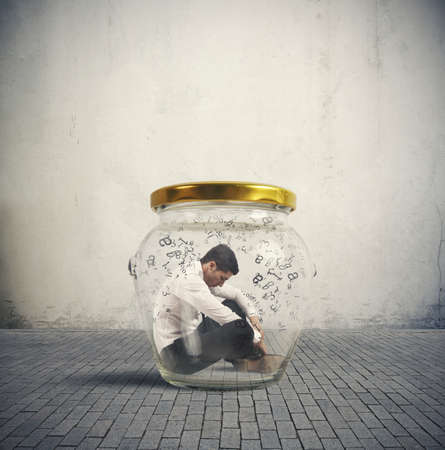 Concept of hermetic businessman closed in a jar photo
