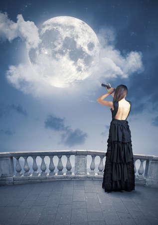 Fashion girl looks the big moon Stock Photo - 21139656