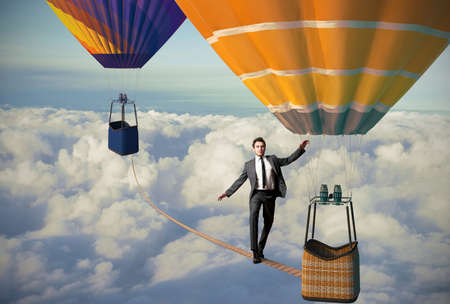 finance problems: Equilibrist businessman over a hot air balloon