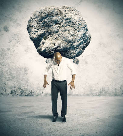 Concept of stress of a businessman with a big rock Фото со стока