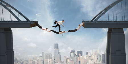 Teamwork concept with running businessman over the bridge Imagens