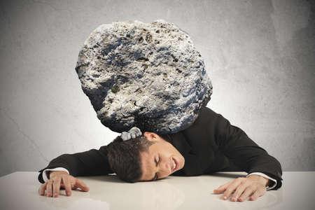 Stress van een zakenman met een grote rots Stockfoto