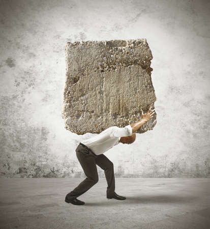 struggling: Concept of stress of a businessman with a big rock Stock Photo