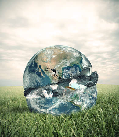 polluted: Concept of garbage with the world in a green field.  Stock Photo