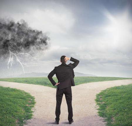 Uomo d'affari ad un bivio con la tempesta e sole