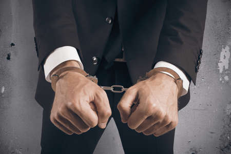 cuffed: Concept of handcuffed businessman in jail Stock Photo