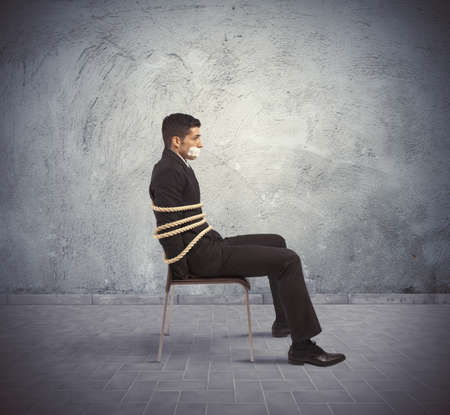 escape: Businessman trapped in a chair with rope Stock Photo