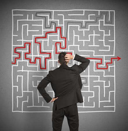 混乱ビジネス男は大きな迷路へソリューションを求めています。