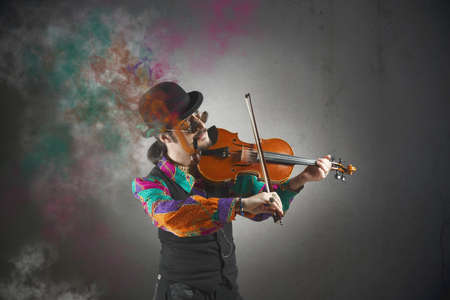 Violinist with pipe surrounded by colorful smoke photo