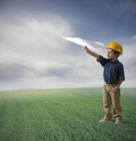 コンセプト: 紙飛行機を飛ばすことを試みる若い男の子