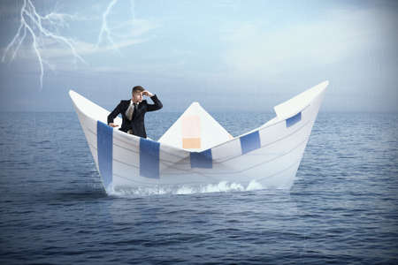 Businessman escapes from the crisis on a paper boat Фото со стока