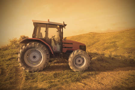 old tractors: Tractor in a field during sunset Stock Photo