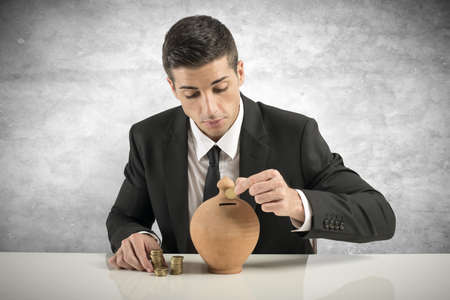 Businessman putting coin into the piggy bank photo