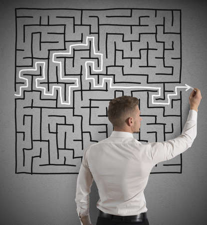 Businessman finding the solution of a maze Imagens