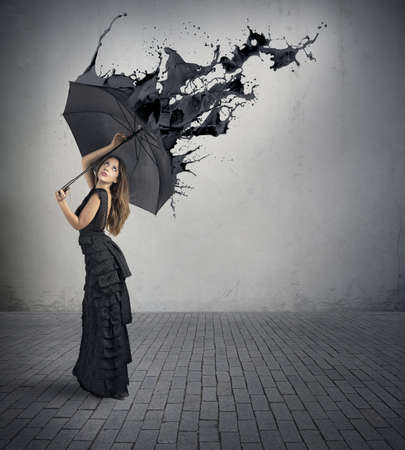 Concept of black color splash with girl holding umbrella photo
