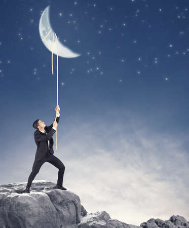 Concept of a businessman that wants the moon Stock Photo