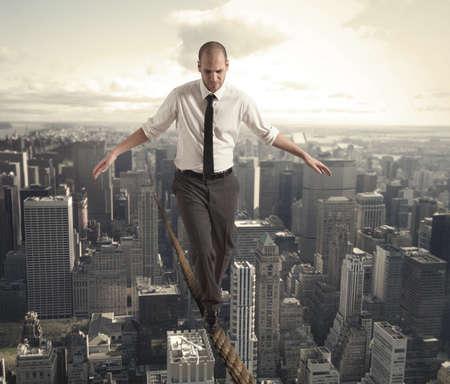 Concept van de moeilijkheden in het bedrijfsleven met equilibrist zakenman