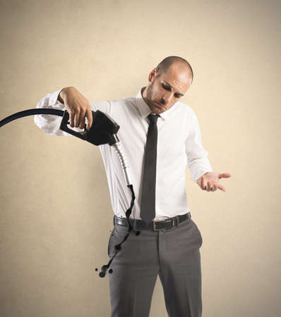 Concept of businessman with pump and lack of fuel photo