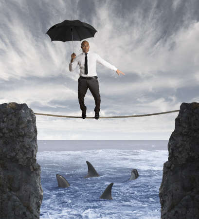 Insurance concept with businessman on a rope and shark in the sea photo