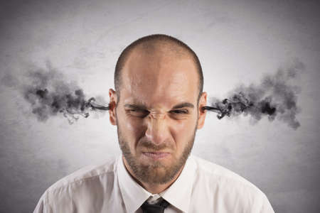 displeased businessman: Concept of stress at work with businessman with smoke