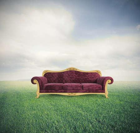 Concept van ontspanning en comfort met een fluwelen rode sofa in een groen gebied Stockfoto