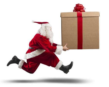 Running santa Claus met een grote gift op een straat Stockfoto