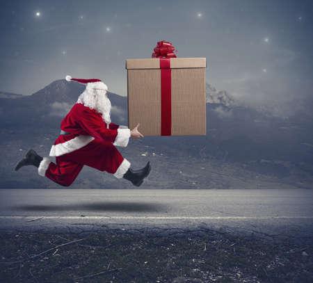 Laufender Weihnachtsmann mit einem großen Geschenk auf einer Straße Standard-Bild - 22501470
