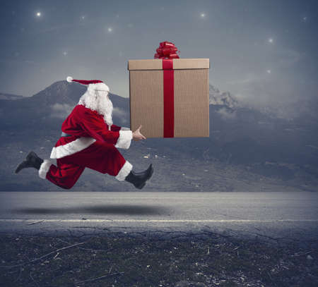 christmas fun: Running santa Claus with a big gift on a street