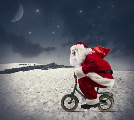 december: Santa claus on the bike in the mountains Stock Photo