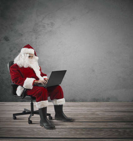 Concept of modern Santa Claus with laptop photo