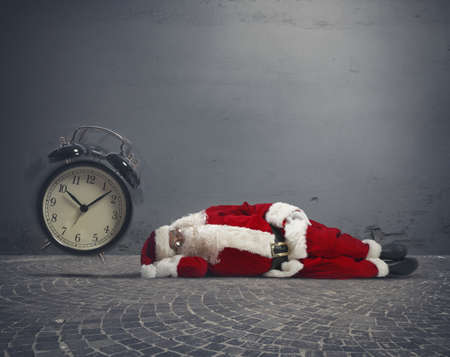 Concept of tired Santa Claus asleep lying on the ground photo