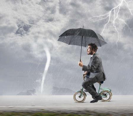 uomo sotto la pioggia: Concetto di fuga dalla crisi con l'imprenditore in bicicletta