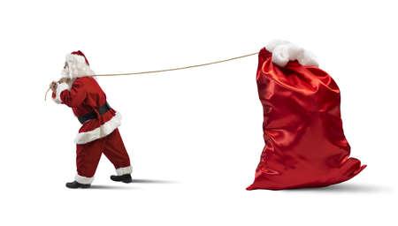 reisen: Weihnachtsmann zieht einen großen Sack voller Geschenke Lizenzfreie Bilder