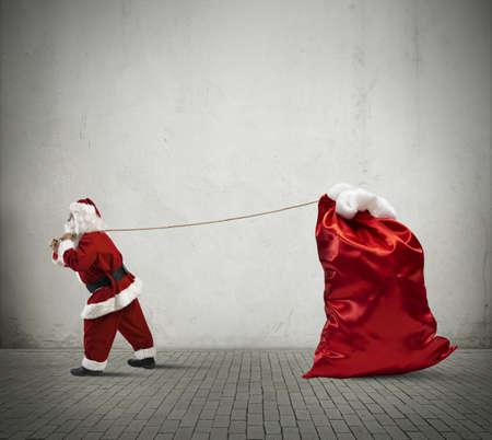 サンタ クロース プレゼントの大きな袋を引っ張る 写真素材