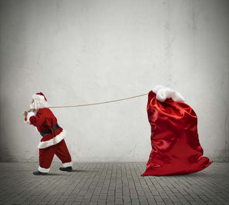 Santa Claus pulls a big sack full of presents photo
