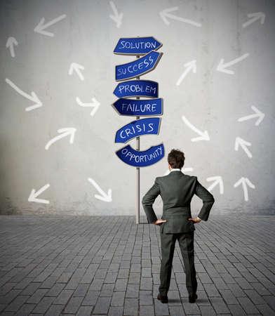 lideres: La confusión de un hombre de negocios en frente de la señal de carretera