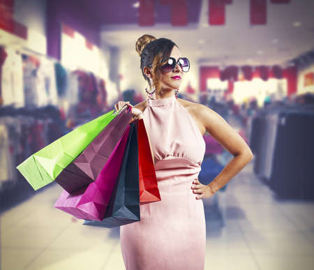 Beautiful young woman holding several shopping bags photo