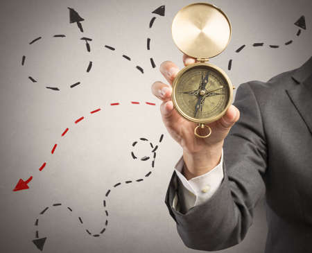 Concept of orientation in the business with businessman and compass photo