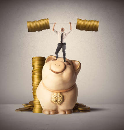 Concept of earning of a businessman who raises money as weights Stock Photo